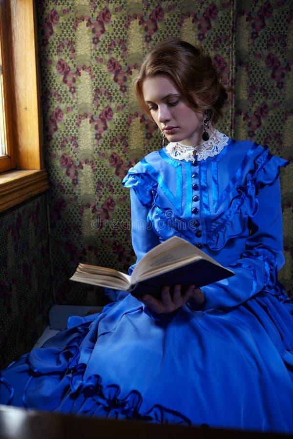 Ung kvinna i blå tappningklänning som läser boken i kupé av r royaltyfria foton