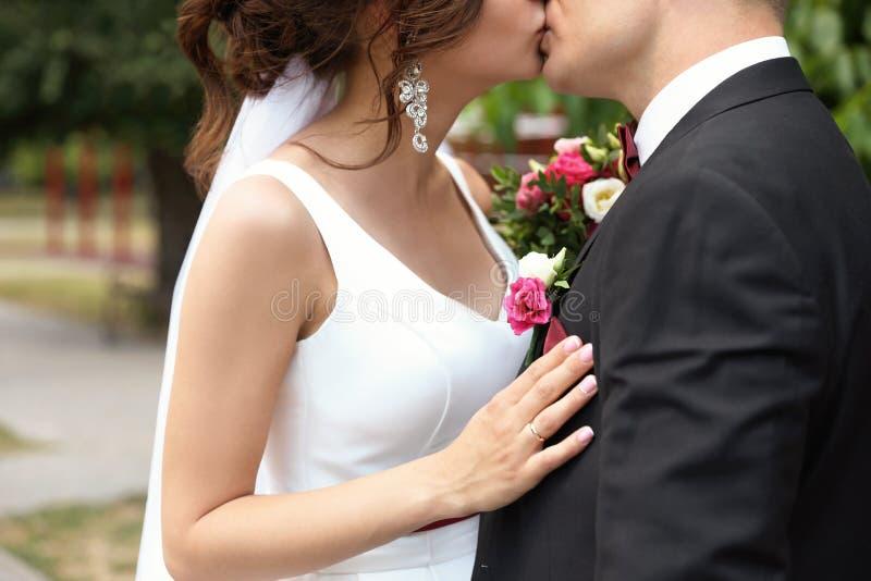 Ung kvinna i bröllopkappa som kysser hennes fiance arkivbild