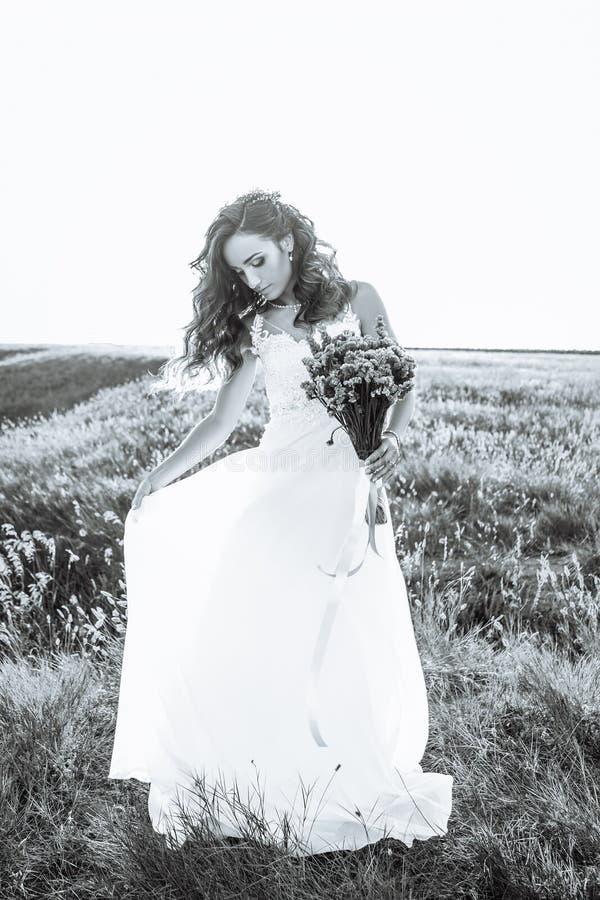 Ung kvinna i bröllopsklänning utomhus royaltyfri foto