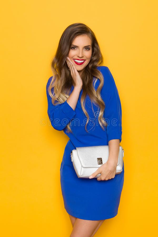 Ung kvinna i den blåa Mini Dress Is Holding Silver handväskan som poserar med handen på Chin And Smiling arkivbilder
