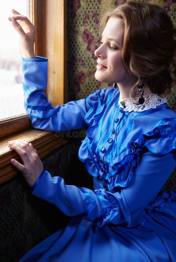 Ung kvinna i den blåa tappningklänningen som ut ser fönstret i direktstöt royaltyfria bilder