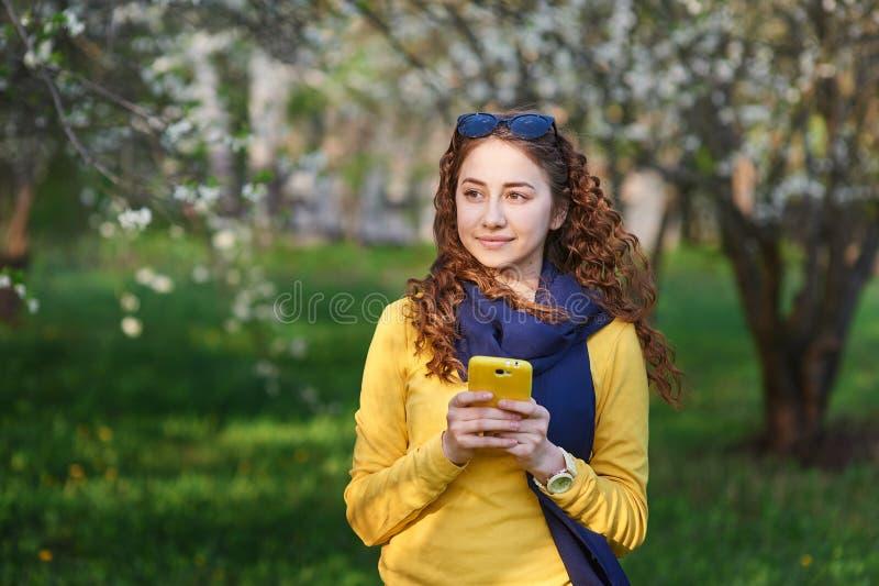 Ung kvinna i den blomstra vårträdgården med smartphonen arkivbilder