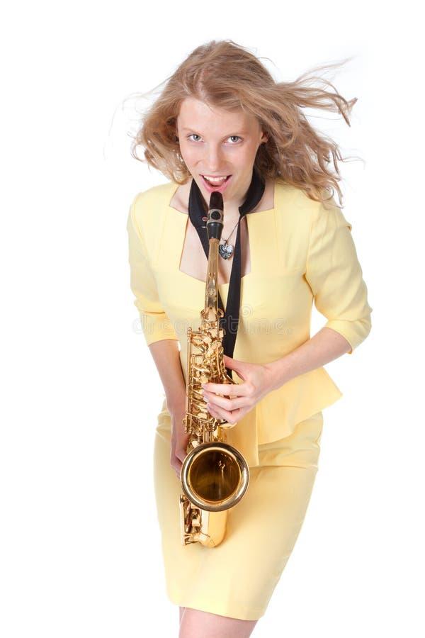 Ung kvinna i den gula mini- klänningen som spelar den alt- saxofonen royaltyfria foton