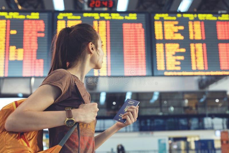 Ung kvinna i den internationella flygplatsen som ser informationsbrädet om flyg royaltyfri fotografi