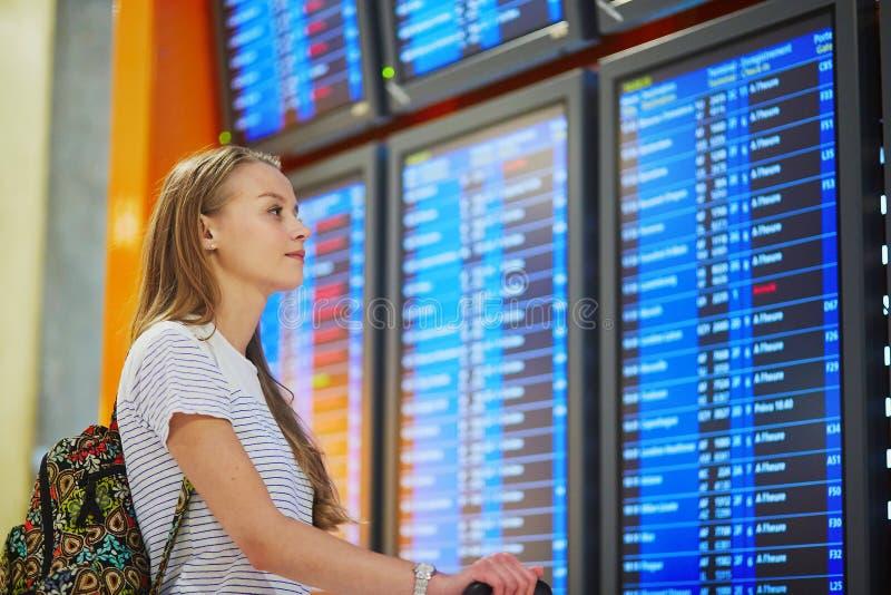 Ung kvinna i den internationella flygplatsen som ser informationsbrädet om flyg royaltyfria bilder
