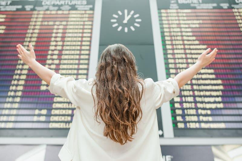 Ung kvinna i den internationella flygplatsen som ser informationsbrädet om flyg som kontrollerar för flyg arkivbilder