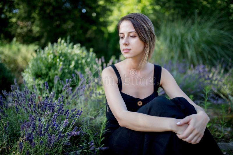 Ung kvinna i den mörka klänningen som sitter nära lavendelblommor royaltyfri foto