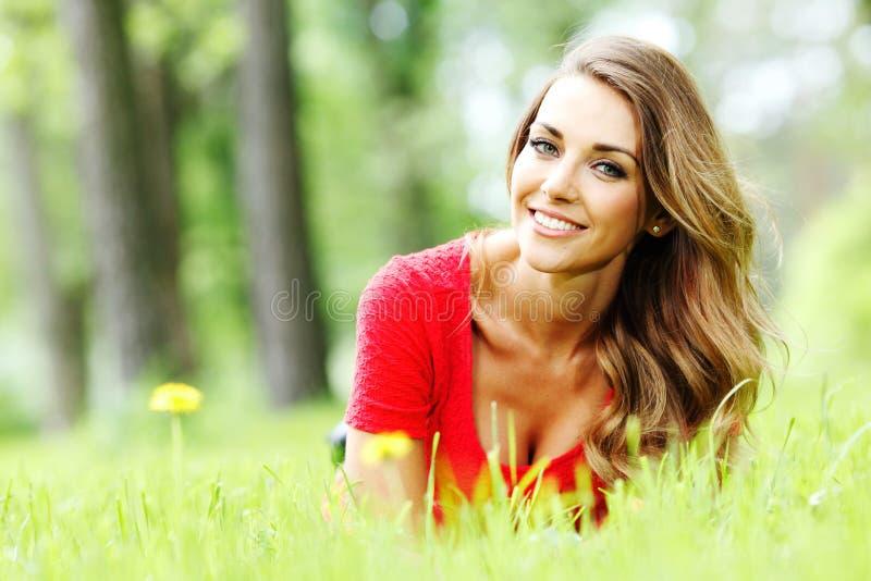 Ung kvinna i den röda klänningen som ligger på gräs fotografering för bildbyråer