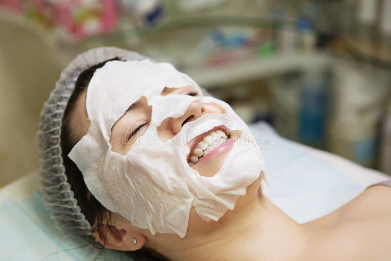 Ung kvinna i den Spa salongen med den ansikts- maskeringen fotografering för bildbyråer