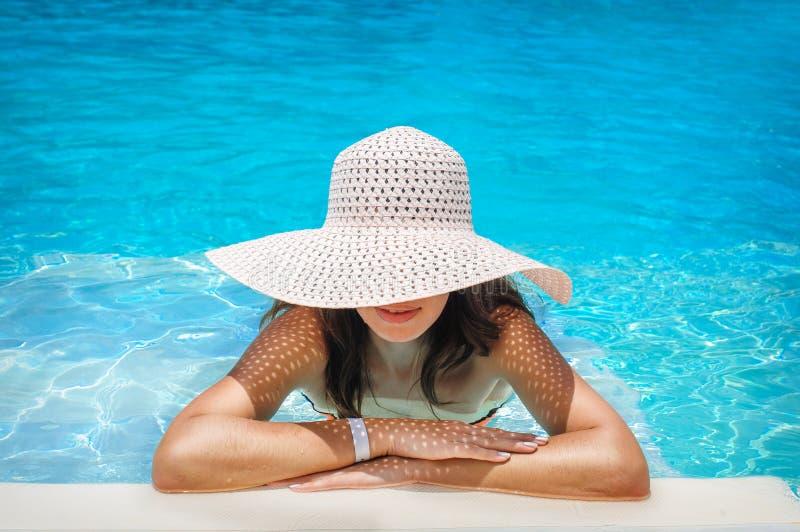 Ung kvinna i den vita hatten som vilar i pöl fotografering för bildbyråer