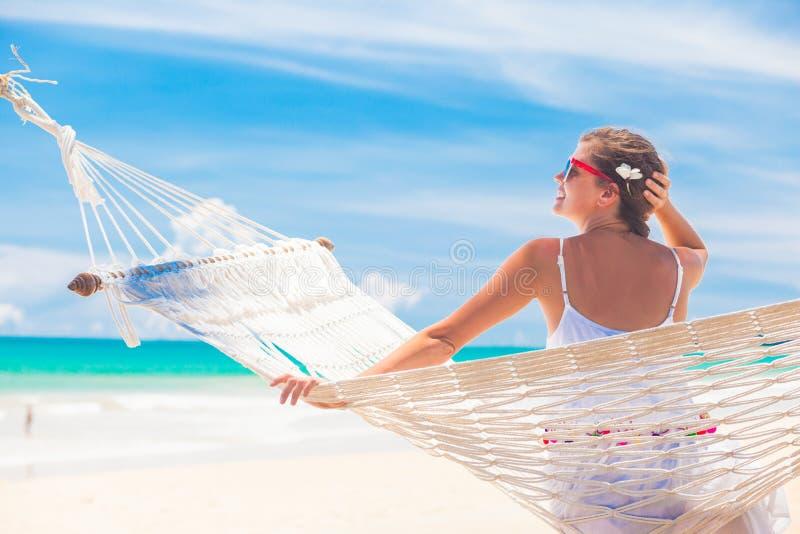 Ung kvinna i den vita klänning- och sugrörhatten som kopplar av i en hängmatta vid stranden arkivbild