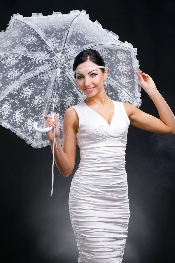 Ung kvinna i den vita klänningen med det vita paraplyet arkivfoto