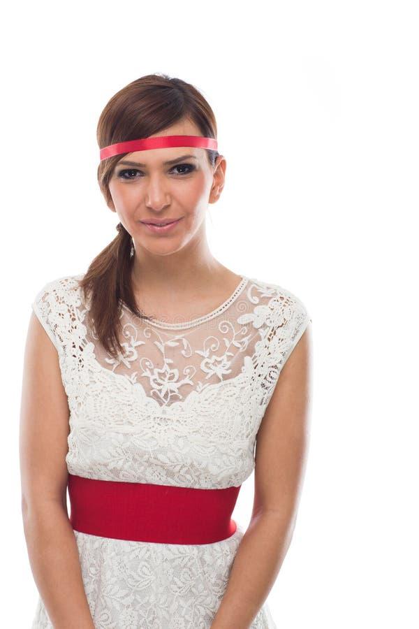 Ung kvinna i den vita klänningen och rött band i huvud royaltyfria foton