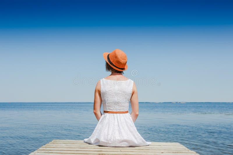Ung kvinna i den vita klänningen som solbadar på sjösidan royaltyfri foto