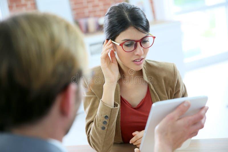 Ung kvinna i det optiska lagret som försöker på glasögon fotografering för bildbyråer