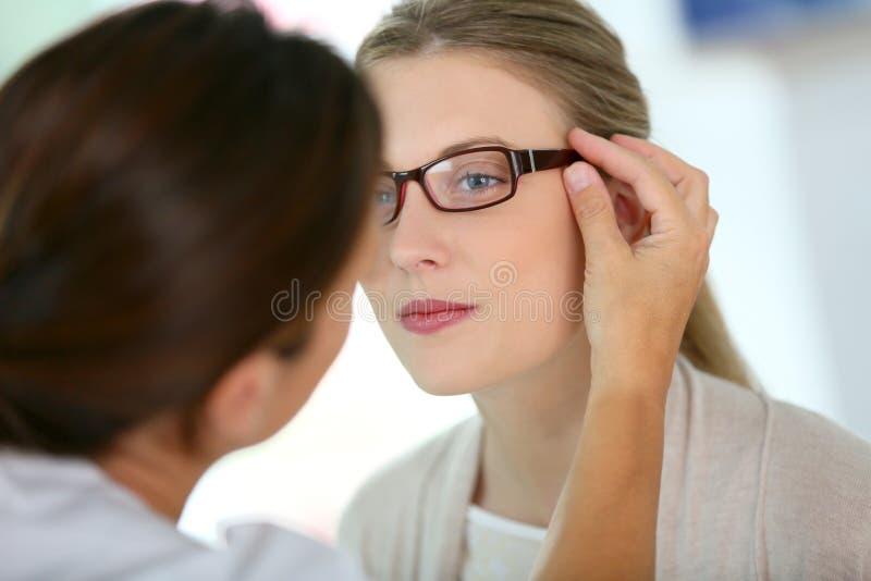 Ung kvinna i det optiska lagret som försöker på glasögon royaltyfri foto