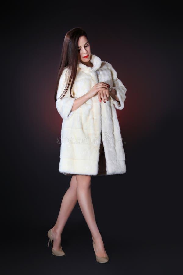 Ung kvinna i det vita pälslaget av minken på svart bakgrund arkivbilder
