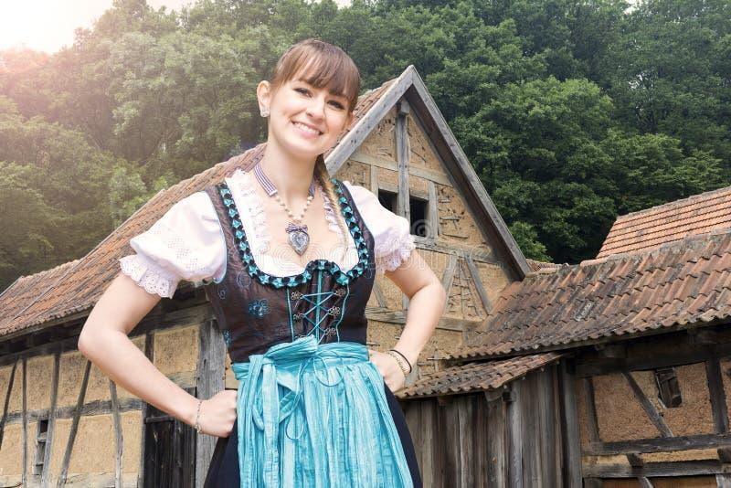 Ung kvinna i dirndl framme av gamla lantgårdhus fotografering för bildbyråer