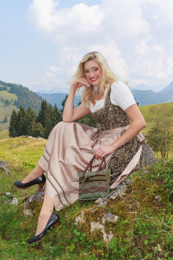 Ung kvinna i dirndlen som sitter i natur på en vagga royaltyfri foto