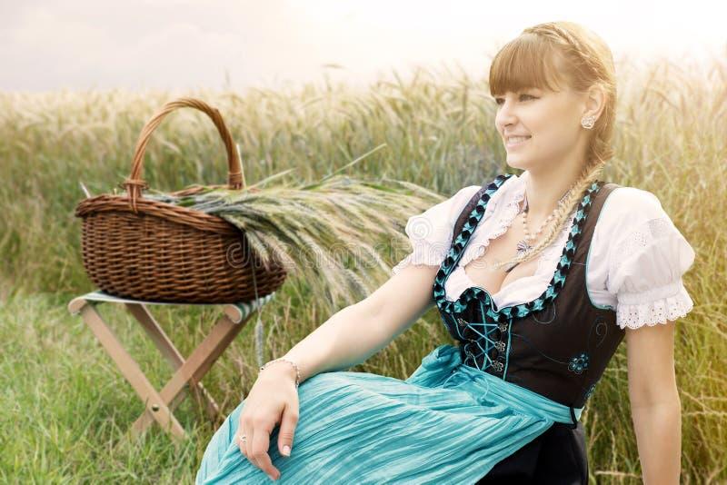 Ung kvinna i dirndlsammanträde på vetefältet royaltyfri fotografi