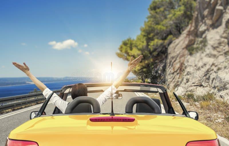 Ung kvinna i en bil på vägen till havet mot en bakgrund av härliga berg på en solig dag arkivbilder