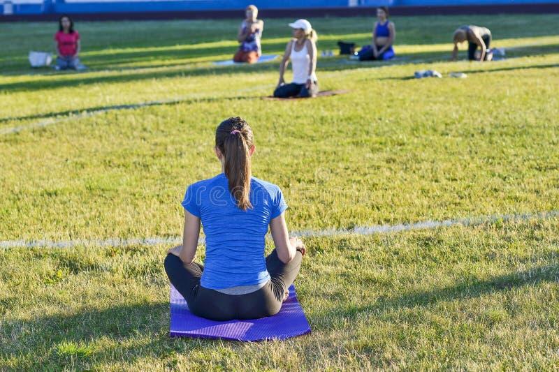 Ung kvinna i en bl? skjorta som g?r yoga i en grupp p? stadsstadion, Ryssland, Kursk region, Zheleznogorsk, Juni 2018 royaltyfria foton