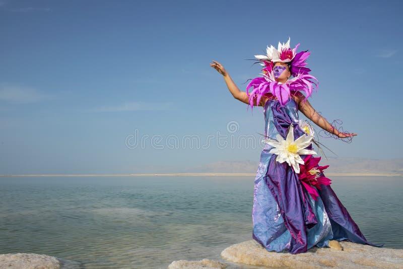 Ung kvinna i en klänning som dekoreras med konstgjorda blommor som står på ett salt bildande arkivfoton