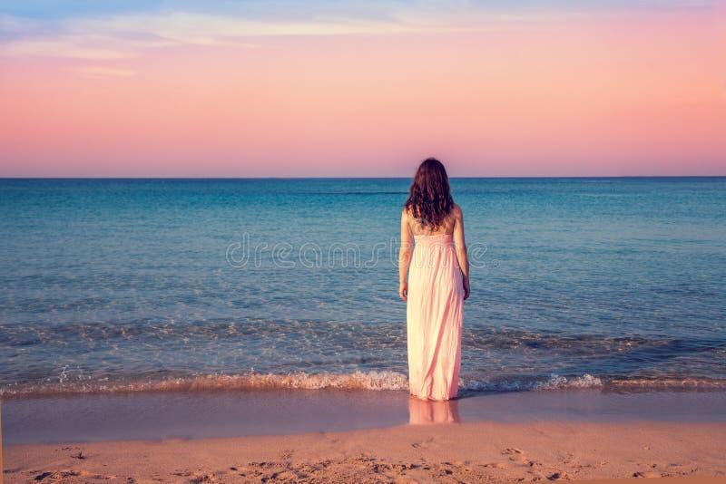 Ung kvinna i en lång klänning på stranden royaltyfria bilder