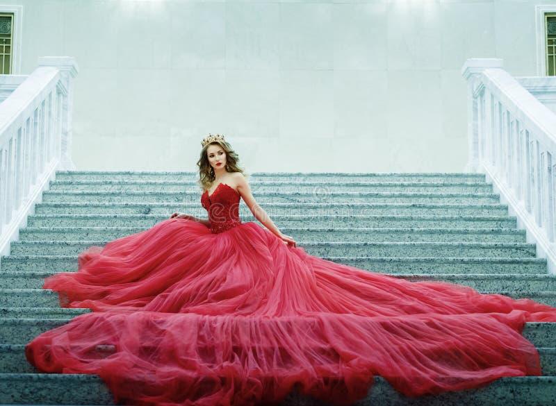 Ung kvinna i en lång röd klänning och guld- kronasammanträde på sten royaltyfri foto