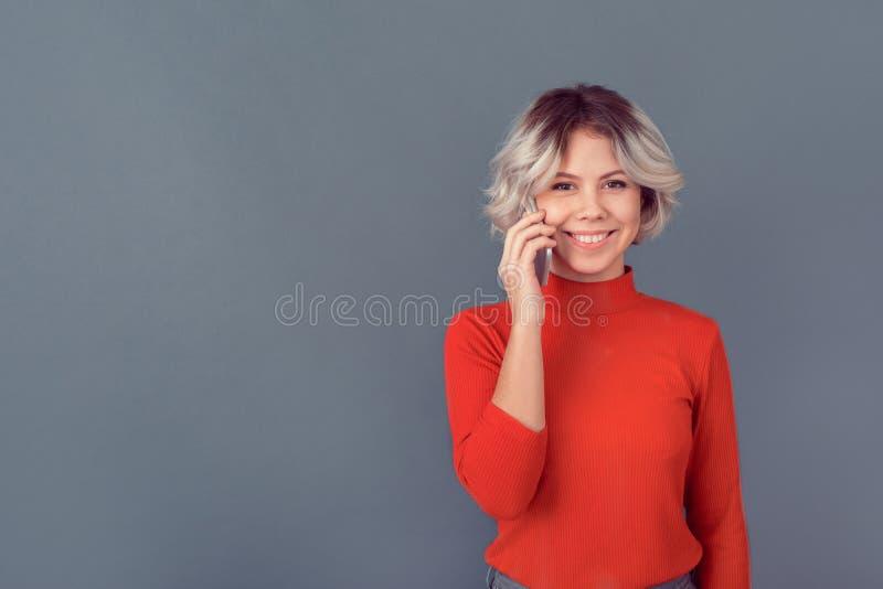 Ung kvinna i en röd blus som isoleras på den gråa väggen som talar av telefonen arkivbild