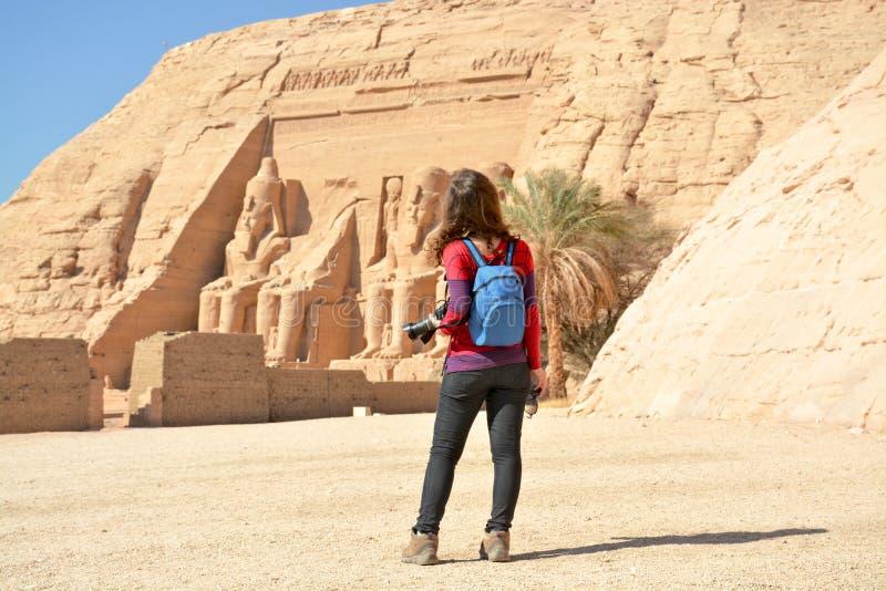 Ung kvinna i en tillfällig klänning som tar foto av den berömda Abu Simbel templet i Egypten på en solig dag royaltyfria foton