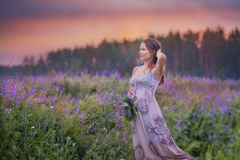 Ung kvinna i ett fält arkivfoto
