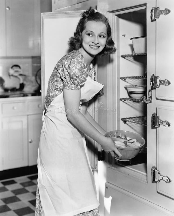 Ung kvinna i ett förkläde i hennes kök som tar mat ut ur kylskåpet (alla visade personer inte är längre uppehälle och ingen est fotografering för bildbyråer