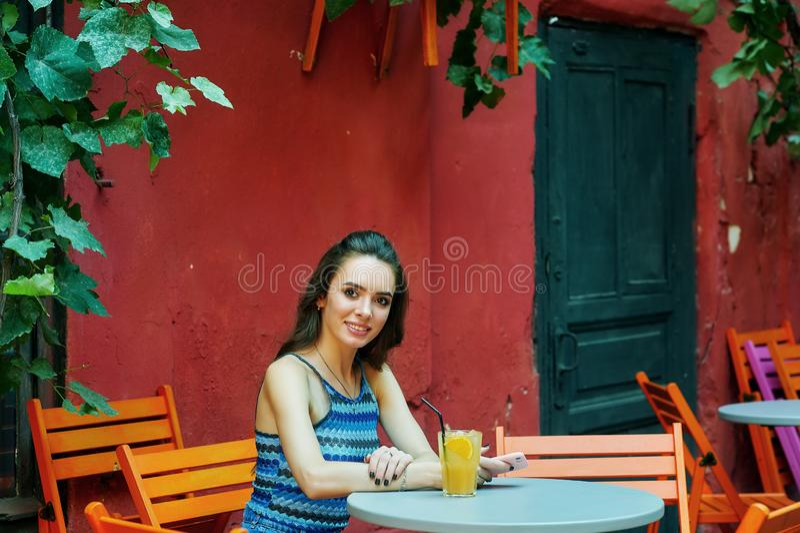 Ung kvinna i ett gatakafé med ett exponeringsglas av den förnyande drinken royaltyfria bilder