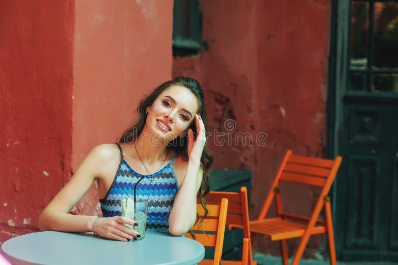 Ung kvinna i ett gatakafé med ett exponeringsglas av den förnyande drinken arkivbild