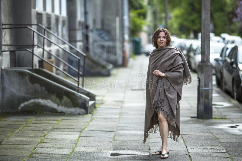 Ung kvinna i ett ponchoanseende i gatan nära huset arkivfoton