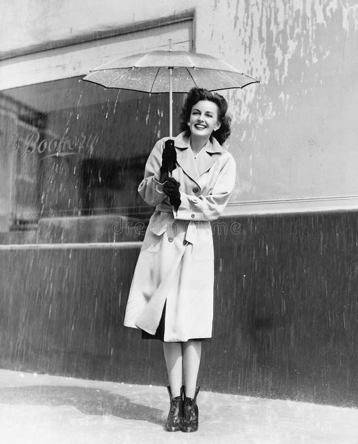 Ung kvinna i ett regnrock- och paraplyanseende i regnet (alla visade personer inte är längre uppehälle, och inget gods finns sup arkivfoton