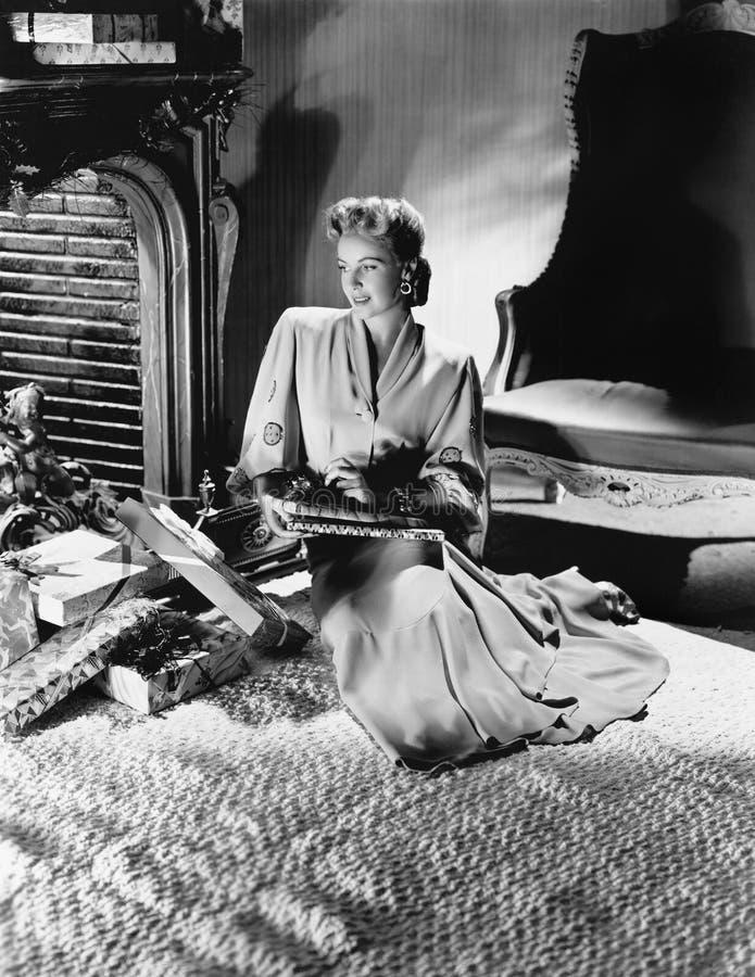 Ung kvinna i ett sammanträde för elegant klänning på en säng med massor av gåvor runt om henne (alla visade personer inte är läng royaltyfria bilder