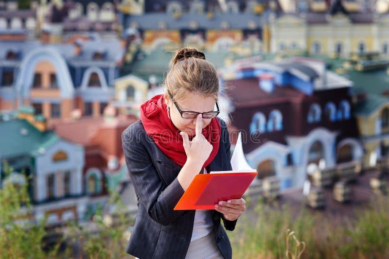 Ung kvinna i exponeringsglas med den röda mappen i händer på bakgrund av staden arkivbilder