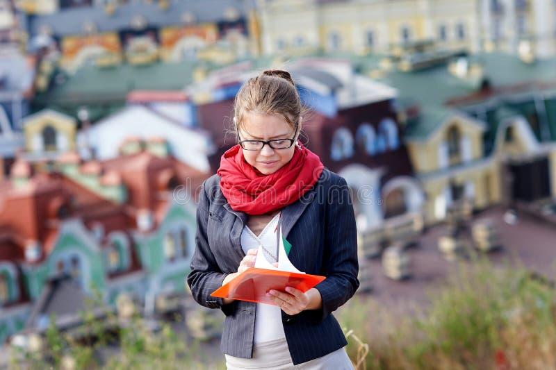 Ung kvinna i exponeringsglas med den röda mappen i händer på bakgrund av staden royaltyfria foton