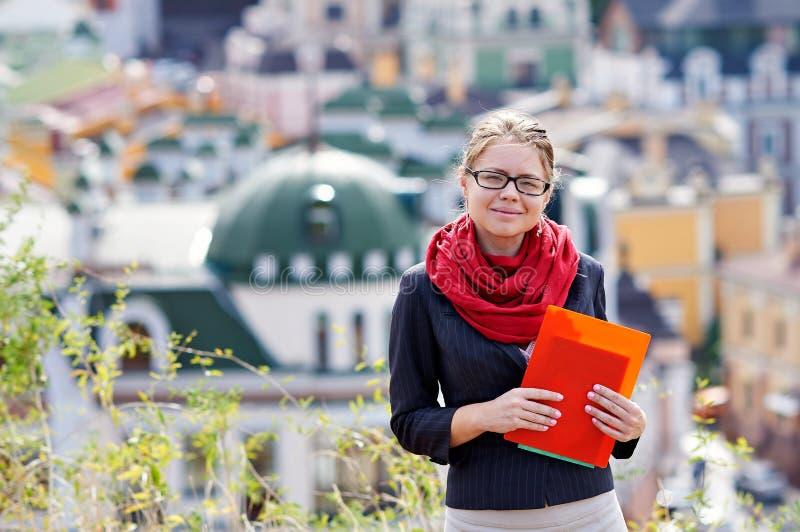 Ung kvinna i exponeringsglas med den röda mappen i händer på bakgrund av staden royaltyfria bilder