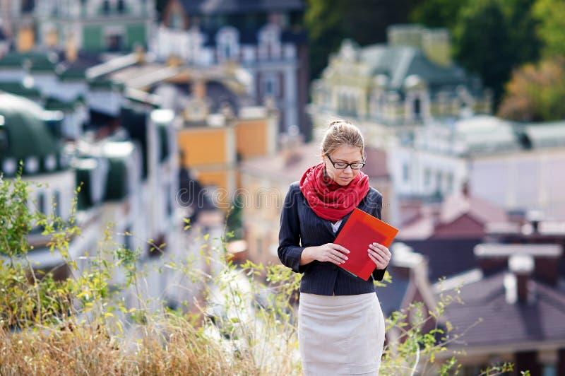 Ung kvinna i exponeringsglas med den röda mappen i händer på bakgrund av staden royaltyfri bild