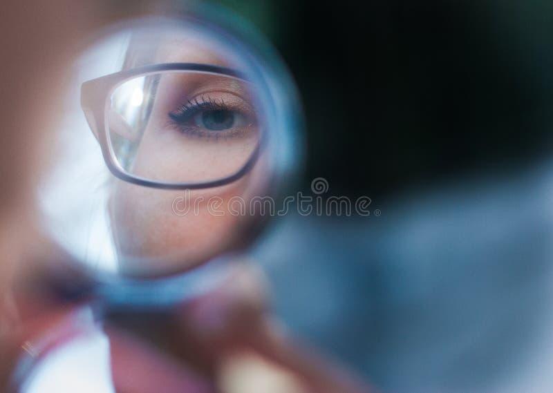 Ung kvinna i exponeringsglas som ser i den kosmetiska spegeln, slut upp royaltyfri bild
