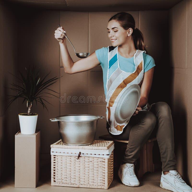 Ung kvinna i förkläde som lagar mat i kartong arkivbilder
