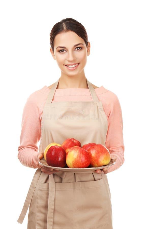 Ung kvinna i förklädeinnehavplatta med saftiga äpplen royaltyfria foton