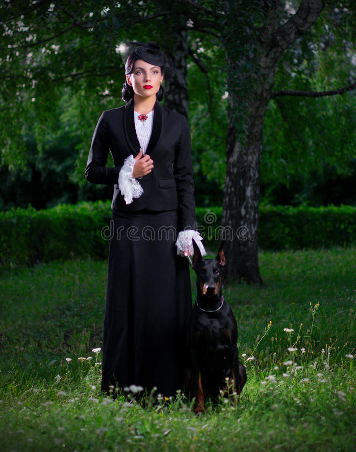 Ung kvinna i forntida dräkt med hunden (normal ver) arkivfoto