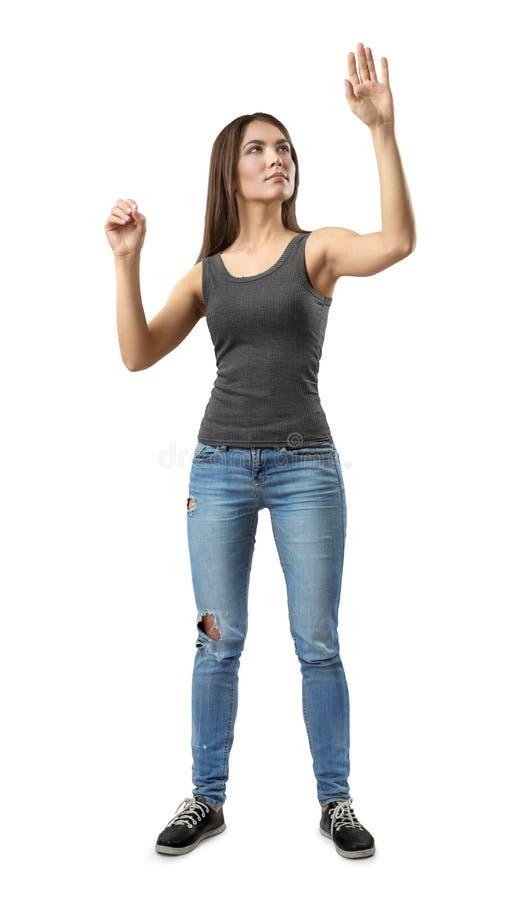 Ung kvinna i gr? ?verkant och jeans som st?r, en hand i ?razziors gest och annan som s? lyfts, om trycka p? som ?r osynligt arkivbilder