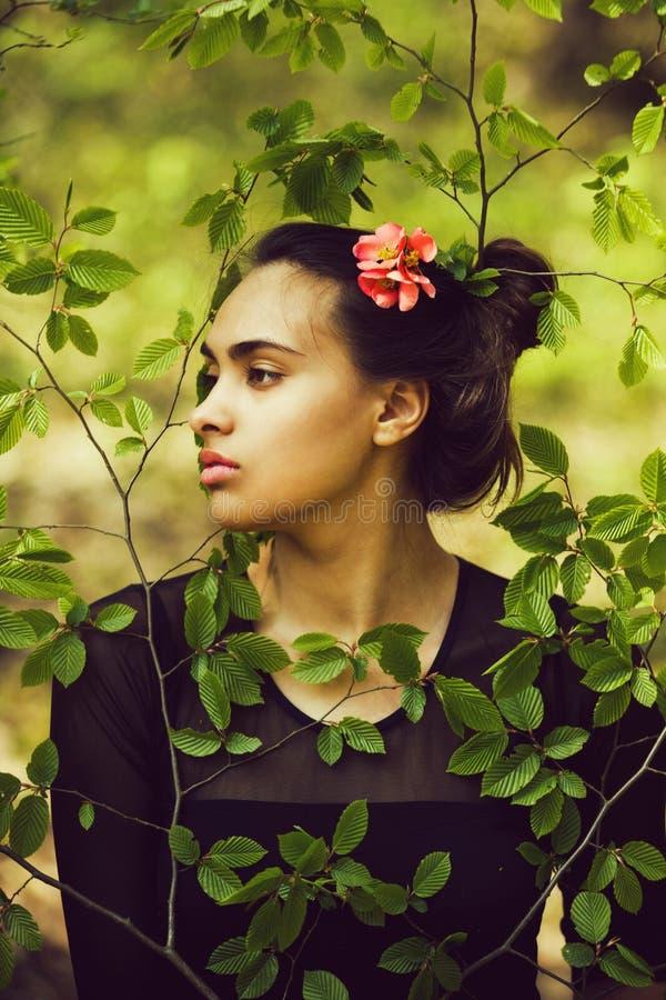 Ung kvinna i gröna sidor i skog på naturbakgrund arkivbild