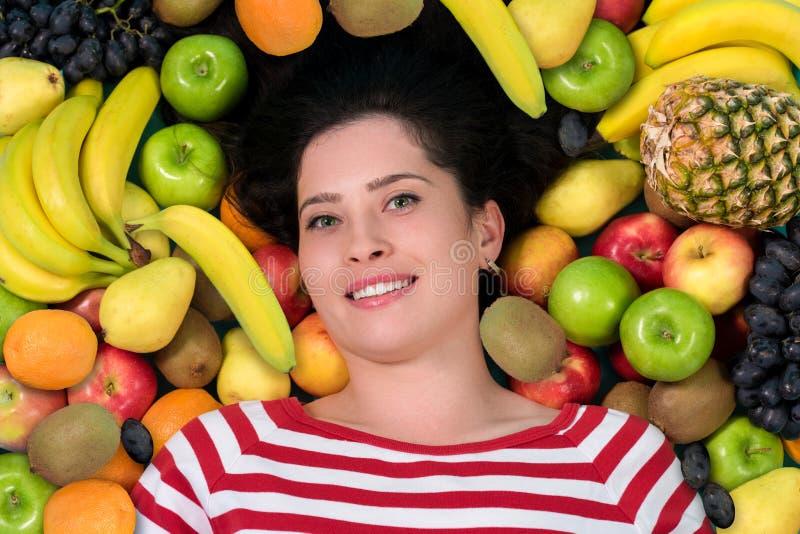 Ung kvinna i grupp av frukt Sjukvård arkivfoton