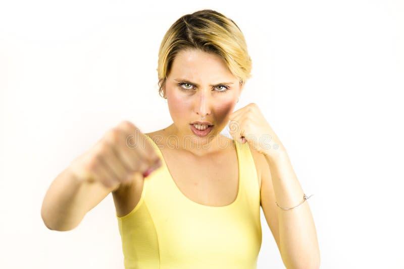 Ung kvinna i gul klänning som stansar med den ilskna framsidan arkivfoto